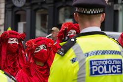 London, UK. 23rd August, 2021. Members of the Extinction Rebellion Red Rebel Brigade line up in front of Metropolitan Police officers in the Covent Garden area during the first day of Impossible Rebellion protests. Extinction Rebellion are calling on the UK government to cease all new fossil fuel investment with immediate effect. Credit: Mark Kerrison/Alamy Live News