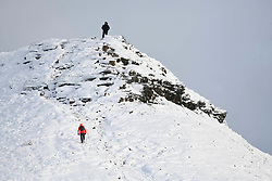 © Licensed to London News Pictures. 04/12/2020. <br /> Two people head to the summit of Corn Du, in the Brecon Beacons, the highest point in southern Wales and England, which has seen it's first snowfall of the year. Photo credit: Robert Melen/LNP