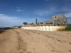EXCLUSIVE: Sella McCartney has infuriated her neighbours in The Hamptons by building a 5ft high sea wall that blocks her community's decades-old private access to its beach. The fashion designer and husband Alasdhair (correct) Willis paid $1.7million for their three-bedroom ocean front home and adjoining land three years ago. But erosion is claimed to have destroyed 40 feet of frontage in just one year so they joined with an adjacent neighbour to build the wall to save both properties. However, the imposing 230ft wide sandbag structure also runs across a beach entrance road between the two homes that is for everyone living in the private avenue. It slopes up on the avenue side but has had a 5ft sheer drop on to the beach since October last year because a storm washed away the sand that made it resemble a dune. This has made it impossible for most of the residents, many of them elderly, to get down on to the beach. Some neighbours, many having lived for decades in the quiet lane in Amagansett, Long Island, New York, have now branded the designer, 47, arrogant and high-handed. Despite The Hamptons being a millionaires' playground with high property prices, most residents in the private avenue have lived there for many years and hold down regular jobs or are retired. Stella and her family are believed to have spent part of last summer at the modest 1176 sq ft home. She has four children with Alasdhair, the creative director at boot brand Hunter. The couple advertised the home as a summer rental in 2017 for up to $30,000 a month. Stella's dad Sir Paul, 77, has had a home in uber-fashionable Amagansett since the 1990s and pal Gwyneth Paltrow, 46, also has a house there. Stella and the neighbour's wall went up in July last year. But her permit with East Hampton council expired in April. She is now applying for a time extension– but is willing to remove the sandbags across the 30ft wide access and run them round the side of her house, according to the latest pape