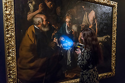 "© Licensed to London News Pictures. 29/11/2019. LONDON, UK. A staff member using a UV light inspects ""The Adoration of the Shepherds"", circa 1614, by Caravaggesque Master (Est. GBP40-60k) at the preview of Old Masters sales at Sotheby's, New Bond Street.  Works will be offered for sale on 4 and 5 December.  Photo credit: Stephen Chung/LNP"