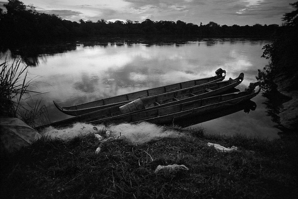 """French guyana, elahe, maroni.<br /> <br /> Depuis 1996, les amerindiens de Guyane ont des papiers d'identite. Ils ont des comptes a la poste et perçoivent maintenant des subsides de l'Etat. Proches de leur environnement naturel, ils continuent a vivre dans un systeme relativement autarcique : chasse, peche, culture de manioc dans les abattis et … RMI pour les cartouches et l'essence des pirogues. La mise en place prefectorale, dans les annees 70, d'une zone arbitraire a acces reglemente qui englobe """" leurs """" territoires veut pourtant les preserver d'une acculturation certaine. Dans ce village Wayana, le taux d'impregnation au mercure depasse le seuil maximum fixe par l'OMS apres la pollution de Minamata."""