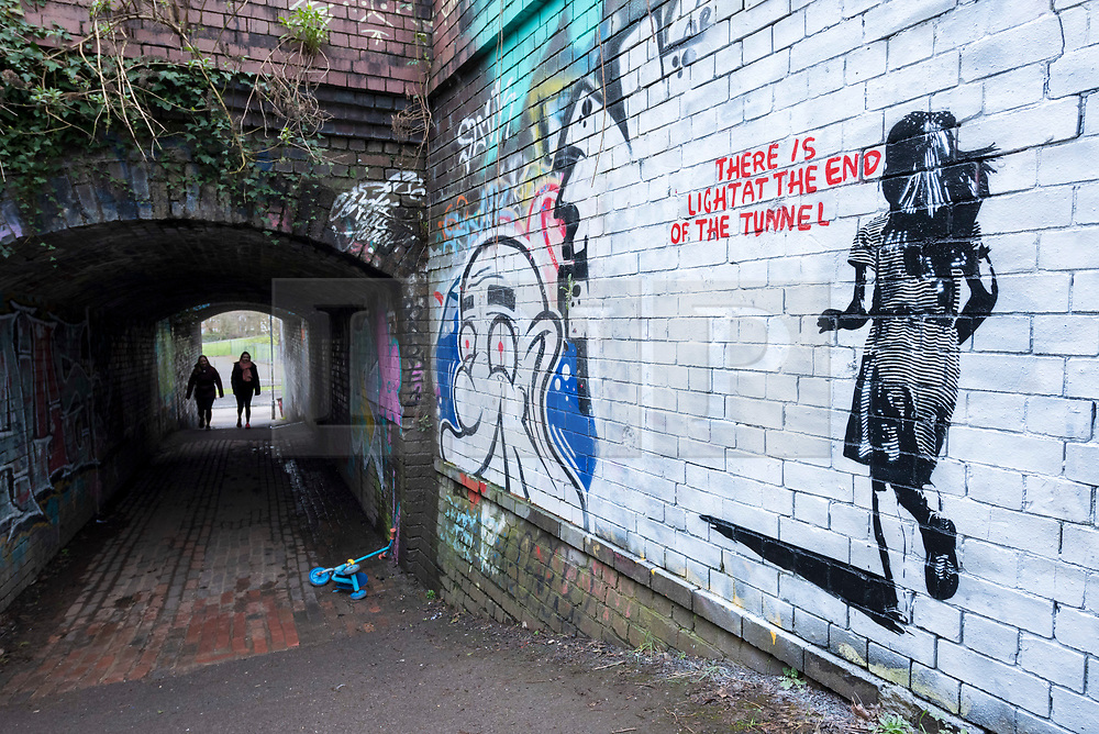 """© Licensed to London News Pictures; 14/03/2021; Bristol, UK. People are seen at the end of a tunnel past a mural in the style of Banksy with an image of a girl and with the words """"There is light at the end of the tunnel"""", by the railway off Muller Road in Bristol. According to some locals it has been painted very recently, perhaps early this morning. Banksy often comments on current events, and if the piece is by Banksy it could be a reference to the end of the covid-19 coronavirus pandemic, or to social movements such as #MeToo, Black Lives Matter, or Reclaim the Streets. Photo credit: Simon Chapman/LNP."""