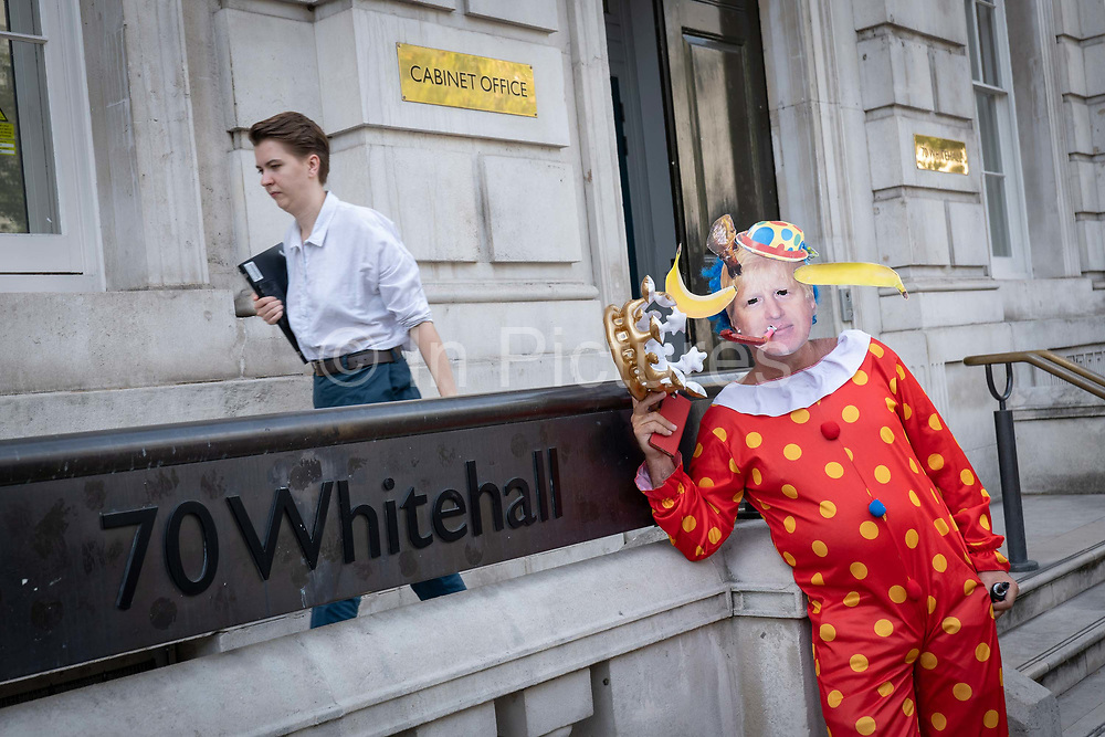 Anti-Brexitcampaigner dressed as a clown impersonates Prime Minister Boris Johnson outside the Cabinet Office on Whitehall on the 29th August 2019 in London in the United Kingdom. A group gather outside the Cabinet Office, protesting against British Prime Minster Boris Johnson's announcement of a suspension of Parliament.