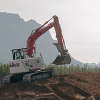 A huge backhoe work on a berm beside the Trans-Canada Highway in Banff National Park, Alberta, Canada.