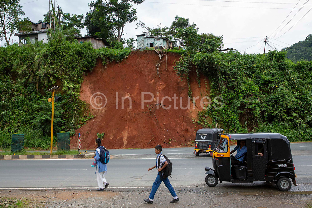 Children walk to school past a mud landslide caused by heavy rainfall along Route 6 on 20th September 2018 in Guwahati, Assam, India.  A motor rickshaw is parked by the side of the road, while another drives away.