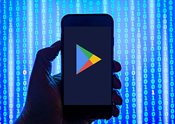 Person holding smart phone with gGogle Play store logo displayed on the screen. EDITORIAL USE ONLY