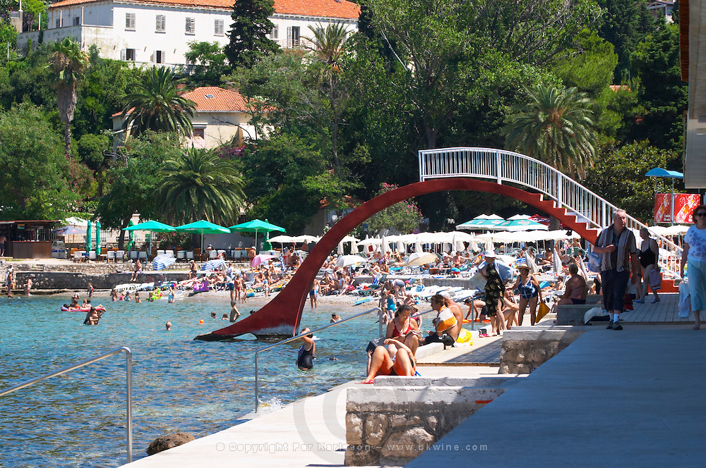 Beach with crowds of tourists and an arched water slide. Uvala Sumartin bay between Babin Kuk and Lapad peninsulas. Dubrovnik, new city. Dalmatian Coast, Croatia, Europe.