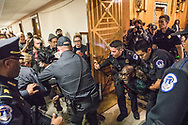 A protestor is arrested for civil disobedience during a Senate hearing on healthcare reform in Washington, D.C. on November 28, 2017. (photo by Erika Nizborski)
