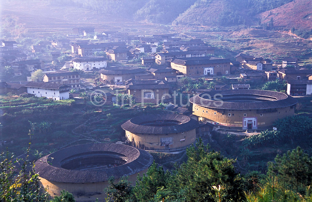 The Chuxi - Hakka- earth dwellings, Chuxi village, Fujian Province.  Interior circular courtyard and living spaces with central water well, shared by residents and chickens and dogs alike. These are some of the most extraordinary multistory structures in China built exclusively out of earth and timber (they are known as tulou). From the outside they look and protect like fortresses, built principally by the ethnic minority group known as the Hakka. They where built principally in the 17th till the early 20th centuries. In all about 1000 remain standing today mostly centered around the mountainous regions of the provinces of Fujian, Jiangxi and Guandong. They where constructed in various shapes from circular, square, oblong,even rhomboid. The Chuxi earth dwellings where built sometime in the Qing Dynasty ( 1644-1912) and still remains well preserved and lived in by a hand full of residents. The single - story inner ring and three -story outer ring are divided into 15 apartments that surround a courtyard  with a water well. Cooking and eating facilities are at ground level and all bedrooms and storage are spread over the upper floors.