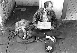 Homeless man with dog sitting on street pavement begging for change with sign stating 'Hungry and Homeless',