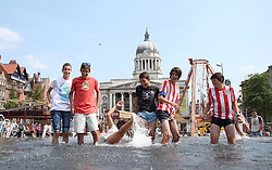 © Licensed to London News Pictures . 17/07/2013 . Nottingham, UK . A group of Spanish students make a splash on the fountail at Market Square House, Nottingham as the heatwave continues across the UK with temperatures soaring to 30 degrees Celsius. Photo credit : /LNP