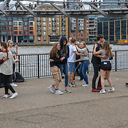 A busker under the Millennium Bridge known at wobbly bridge tourists dancing to te music, on 18 July 2019, City of London, UK.