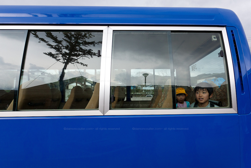 Two elementary school students  sit in the back of a minibus as they leave at the end of the day. Kawauchi Elementary School, Kawauchi, Fukushima, Japan. Tuesday April 30th 2013. Kawauchi was evacuated after the accidents at Fukushima Daichi nuclear plant but has been nominally decontaminated and some of the school children have returned to classes.