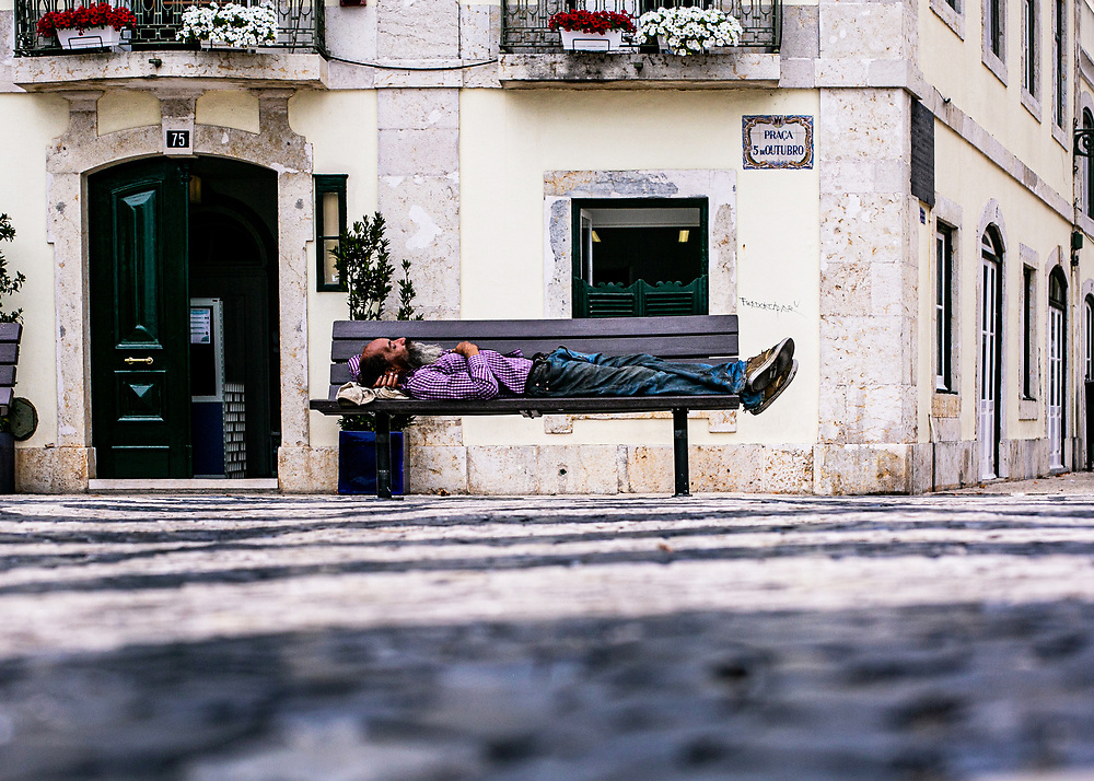 A man sleeps on a bench in the centre of Lisbon, Portugal, during the Summer of 2020 as a pandemic still rages world wide. Credit: Narra Fortin/UoG/Pathos Images.
