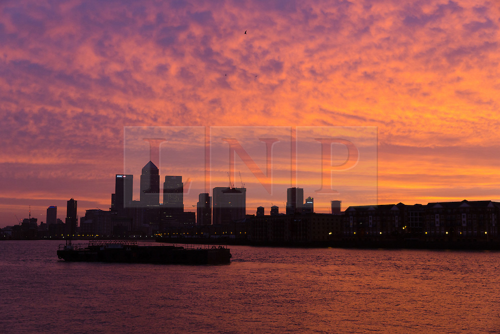 © Licensed to London News Pictures. 24/12/2016. LONDON, UK.  Pink and orange sky is seen on the River Thames, behind the Canary Wharf financial district just before sunrise this morning. The weather in London is feeling unseasonably warm this morning. Photo credit: Vickie Flores/LNP