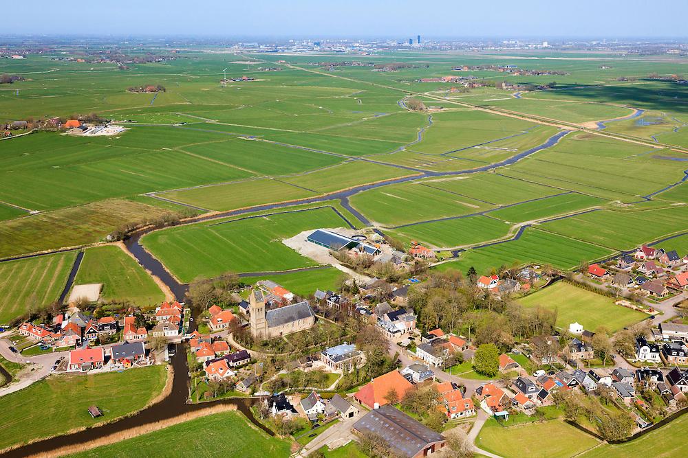 Nederland, Friesland, Gemeente Littenseradeel, 01-05-2013; Jorwerd (Jorwert), dorp met Hervormde kerk met toren en kerkhof (Sint-Radboudkerk). Bekend van het boek van schrijver Geert Mak 'Hoe God verdween uit Jorwerd'. Skyline Leeuwarden in de achtergrond.<br /> Small village with church in Friesland (featuring in well knwn reportage).<br /> luchtfoto (toeslag op standard tarieven)<br /> aerial photo (additional fee required)<br /> copyright foto/photo Siebe Swart