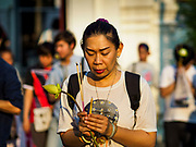 "01 MARCH 2018 - BANGKOK, THAILAND: A woman prays at Wat Pathum Wanaram in central Bangkok. Many people go to temples to perform merit-making activities on Makha Bucha Day, which marks four important events in Buddhism: 1,250 disciples came to see the Buddha without being summoned, all of them were Arhantas, or Enlightened Ones, and all were ordained by the Buddha himself. The Buddha gave those Arhantas the principles of Buddhism. In Thailand, this teaching has been dubbed the ""Heart of Buddhism.""    PHOTO BY JACK KURTZ"