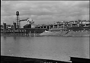 """ackroyd_05924-08. Progress. 2 shots of grain elevator site viewed from across the river,shorter lens. March 15, 1955 5x7"""""""
