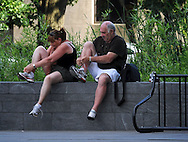 A Couple of Italian tourists adjust their shoes at the American Indian Museum in Washington D.C.