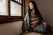 JAPAN, TOKYO Antique Kimono Oshima Tsumugi type from Amami Oshima in Okinawa. The kimono is made by woven natural brown hempy fabric, and the obi is red with embrodery flowers. Photo in Ryokan in a tatami room  - June 2014