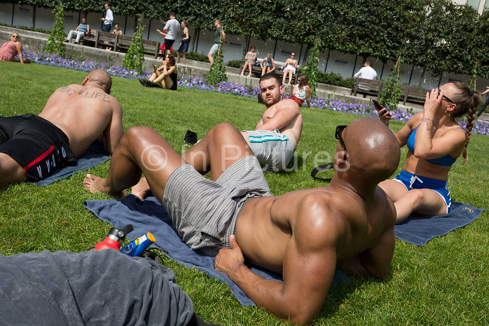 As heatwave temperatures climb to record levels - the hottest day of the year so far, office co-workers sunbathe on the grass beneath St. Pauls Cathedral in the City of London the capitals financial district aka the Square Mile, on 25th July 2019, in London, England.