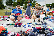 """19 JULY 2020 - DES MOINES, IOWA: Volunteers HAYLEY PRATT, left, and ALLISON PETERSEN sort donated clothing before """"A Celebration of Black Motherhood"""" in Des Moines Sunday. The event was organized by the Supply Hive and Black Lives Matter. Items were donated by members of the community and redistributed to at risk families. They distributed diapers, sanitary products, clothes, books, and toys. They had enough material to help 200 families.       PHOTO BY JACK KURTZ"""