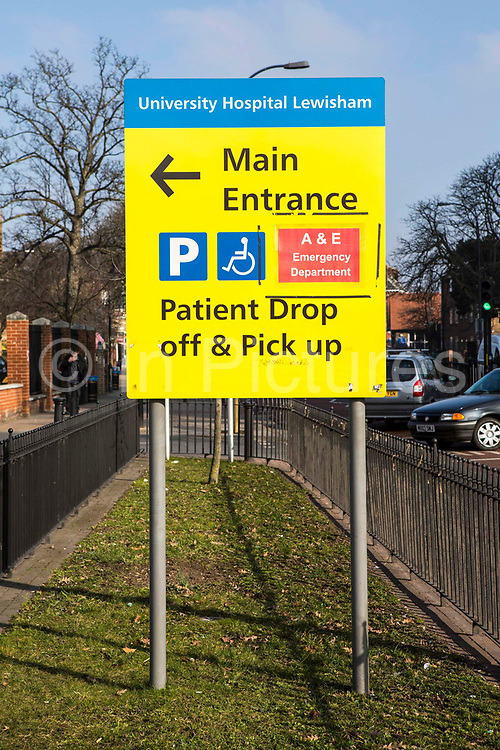 A yellow road sign directing people to University Hospital Lewisham main entrance, parking, accident and emergency department and patient drop off and pick up area, London, UK.