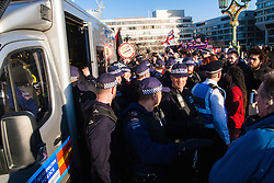 London, March 7th 2015. Following the Climate march through London, masked anarchists and environmental activists clash with police following a breakaway protest at Shell House. PICTURED: Police surround one of their vans as activists attempt to free one of their number after his arrest.