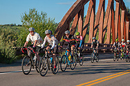 Brad and Hannah Bingham lead a group of cyclists over a bridge at the start of the 2019 Tour de Steamboat.