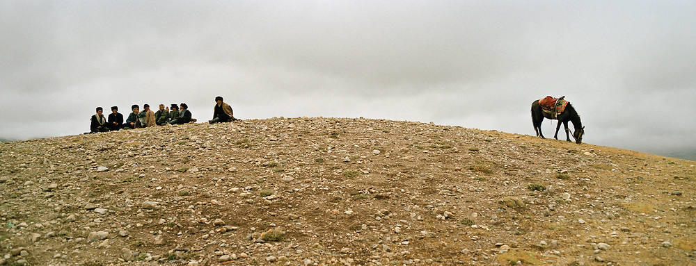"""A group of men beside a lonely horse wait for the start of the Buzkachi. <br /> Buzkachi (traditional afghan horse game) played in Utsch Delgha (""""three valleys"""") previous to a Kyrgyz wedding ceremony. Due to the high altitude, horses can not be bred in the Little Pamir. They are brought from the lower elevations especially Badakhshan region and the Wakhan corridor.<br /> <br /> Adventure through the Afghan Pamir mountains, among the Afghan Kyrgyz and into Pakistan's Karakoram mountains. July/August 2005. Afghanistan / Pakistan."""
