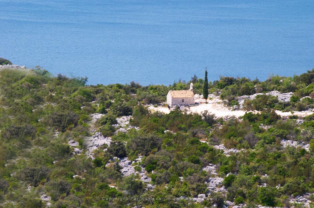 A small chapel overlooking the sea on the coast. A single cypress tree. Dry arid hill side. Dubrovnik region. Dalmatian Coast, Croatia, Europe.