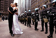 Newlyweds David and Katie Flores kiss as Chicago Police monitor a war demonstration Saturday, April 5, 2003 in Chicago's Federal Plaza.