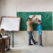 A young student and his teacher in a class room.