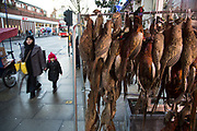 Pheasants hanging up outside a traditional British butchers shop on Bethnal Green Road, London, UK. Once a White British area, the multicultural mix here is predominantly made up of Bangladeshi and other ethnic groups, which seems almost at odds with the areas diversity.