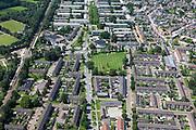 Nederland, Overijssel, Hengelo, 30-06-2011; Klein Driene, wederopbouwwijk, ontworpen in jaren '50. Kenmerkend zijn de open verkaveling van rechte blokken en het groene karakter van de wijk. Het traditionele deel (onder in beeld) uitgevoerd in baksteen en met schuine daken. Boven het meer moderne deel, met betonstructuren en platte daken. In het midden de St. Raphaëlkerk (H.J. van Wissen0.Klein Driene, post-war reconstruction neighborhood, designed in the '50s. Characterized by the open structure of straight building blocks and the green character of the neighborhood..luchtfoto (toeslag), aerial photo (additional fee required).copyright foto/photo Siebe Swart