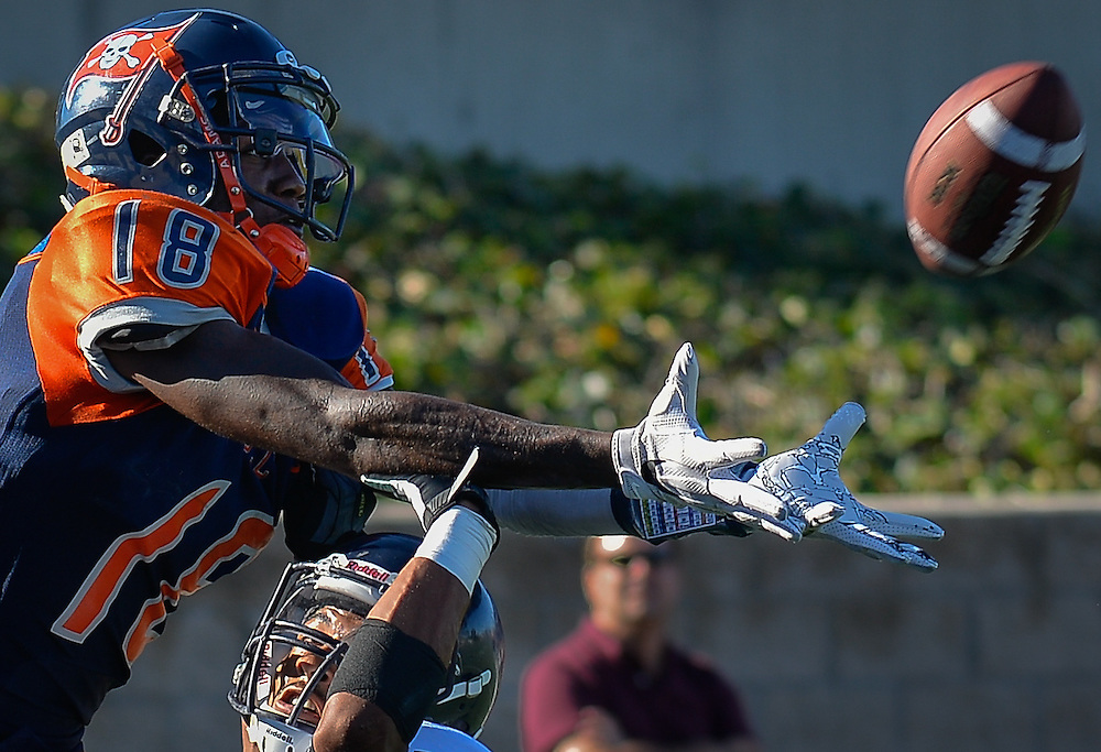 Orange Coast Pirate wide receiver James Rutledge (18) leaps over Fullerton Hornet running back Anthony Wood (8) to complete the reception during the game played in Costa Mesa, California, Saturday, Nov 5, 2016. Photo By: Bryan Woolston, Sports Shooter Academy