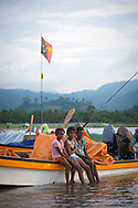 Three girls sit on the side of a boat at the shore in Vanimo, West Sepik Province, Papua New Guinea. (July 18, 2017)