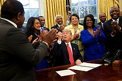 U.S. President Donald Trump gives a pen after signing the HBCU Executive Order to support Black Colleges and Universities in the Oval Office of the White House, February 28, 2017. (pool / Aude Guerrucci)
