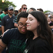 CHARLOTTE NC - MAY 1: Kristine Slade, a student and campus volunteer, (left) embraces Jennifer Tisdale, also a student at the school, after Kristine  became emotional as she spoke to the crowd at a  candle light vigil honoring the victims of a shooting the day earlier on the University of North Carolina Charlotte campus in University City, Charlotte, NC on April 30, 2019.  (Logan Cyrus for AFP)