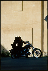 The Kiss. Deadwood, SD. 1993<br /> <br /> Limited Edition Print from an edition of 50. Photo ©1993 Michael Lichter.<br /> <br /> The Story: There is nothing like taking a ride with your love.  No other public moment, even dancing, puts a man and woman so close. The wind in your face and exposed to the elements, hard pavement just below. The bond tightens.