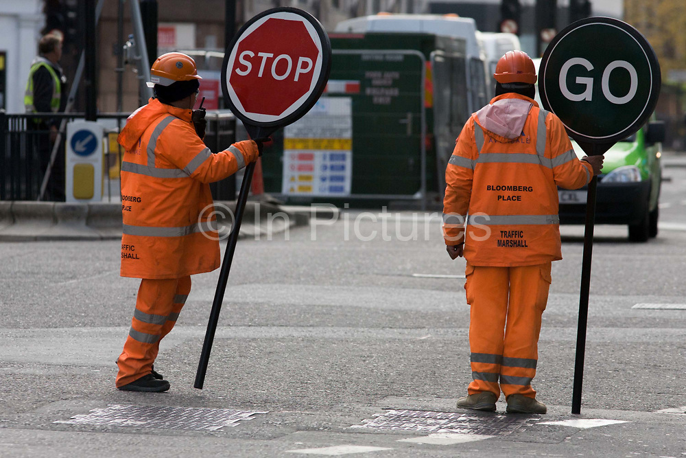 Construction site traffic marshals show conflicting information to oncoming traffic in the City of London. Holding the lollipop signs that say Stop and the saying Go, they wear high-visibility suits at this busy junction directing vehicles as they pass the construction site in the heart of the capital's financial district.