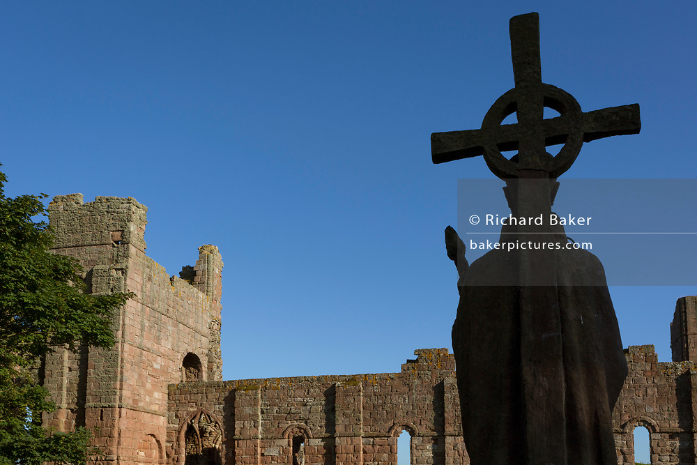 The statue of St. Aidan of Lindisfarne by the artist kathleen Parbury (1958) and the ruined walls of Lindisfarne priory, on Holy Island, on 27th June 2019, on Lindisfarne Island, Northumberland, England. The Holy Island of Lindisfarne, also known simply as Holy Island, is an island off the northeast coast of England. Holy Island has a recorded history from the 6th century AD; it was an important centre of Celtic and Anglo-saxon Christianity. After the Viking invasions and the Norman conquest of England, a priory was reestablished.