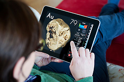 Woman using iPad tablet computer to study chemistry of gold using science application of the Periodic Table