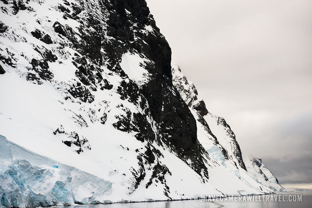 """Steep rocky cliffs reach down to the waterline of the Lemaire Channel on the western coast of the Antarctic Peninsula. The Lemaire Channel is sometimes referred to as """"Kodak Gap"""" in a nod to its famously scenic views."""