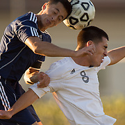 Fullerton, CA - Santa Ana College freshman forward Derian Lopez (blue) and Fullerton College sophomore midfielder Manual Gonzalez (white) head the ball during the college's soccer match held November 7th. Santa Ana went on to win the game 2-0.