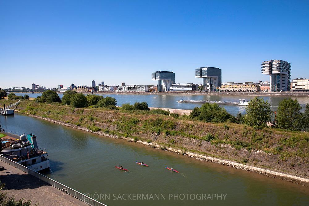 the Rhine harbor in the district Deutz, in the background the river Rhine and the Crane Houses at the Rheinau harbor, Cologne, Germany.<br /> <br /> der Deutzer Hafen, im Hintergrund der Rhein und die Kranhaeuser im Rheinauhafen, Koeln, Deutschland.
