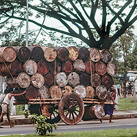 Men push a cart topheavy with oil drums in  Dhaka, Bangladesh in 1977.