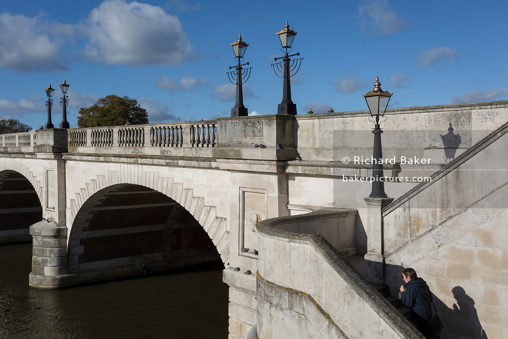 Seen from the southern bank of the river Thames is the architecture of Kingston Bridge where a pedestrian climbs its steps, on 7th November 2019, in Kingston, London, England. A crossing has existed at Kingston since ancient times and this version of Kingston Bridge was constructed by Herbert for £26,800 and opened by the Duchess of Clarence (the future Queen Adelaide) on 17 July 1828. Constructed from Portland stone, it comprises of five elliptical arches.