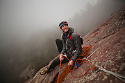 Obadiah Reid belays the photographer on a climb of the First Flatiron (Direct East Face, 5.6) above Boulder, Colorado.