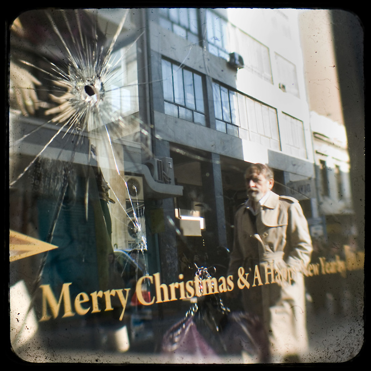 A man passing by a smashed shop front on Ermou Street. <br /> <br /> Following the murder of a 15 year old boy, Alexandros Grigoropoulos, by a policeman on 6 December 2008 widespread riots, protests and unrest followed lasting for several weeks and spreading beyond the capital and even overseas<br /> <br /> When I walked in the streets of my town the day after the riots I instantly forgot the image I had about Athens, that of a bustling, peaceful, energetic metropolis and in my mind came the old photographs from WWII, the civil war and the students uprising against the dictatorship. <br /> <br /> Thus I decided not to turn my digital camera straight to the destroyed buildings but to photograph through an old camera that worked as a filter, a barrier between me and the city.